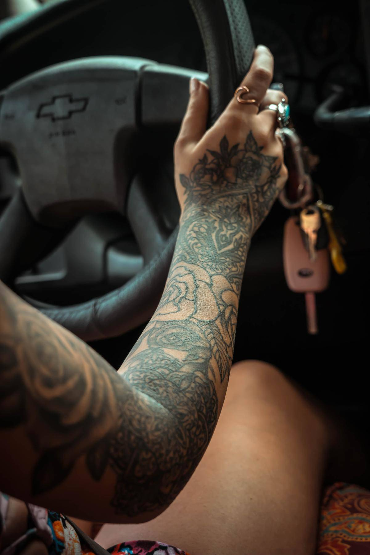 Close-up of tattooed woman driving her car
