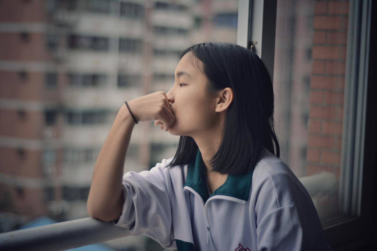 Young woman looks out window at city