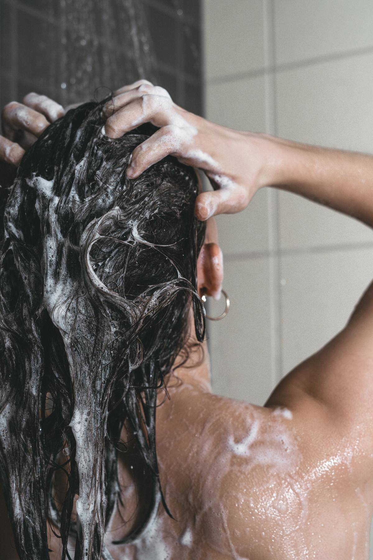 Woman lathering hair in shower