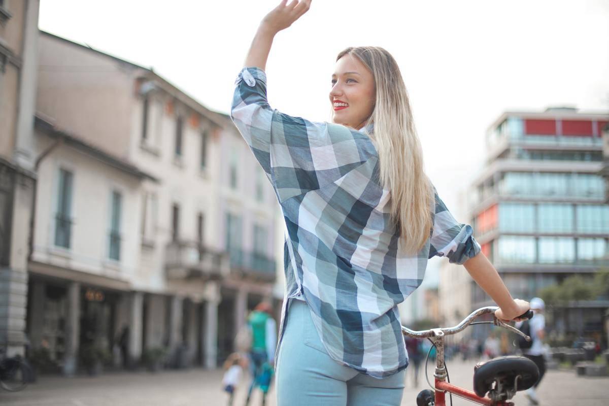 Woman waves goodbye over her shoulder