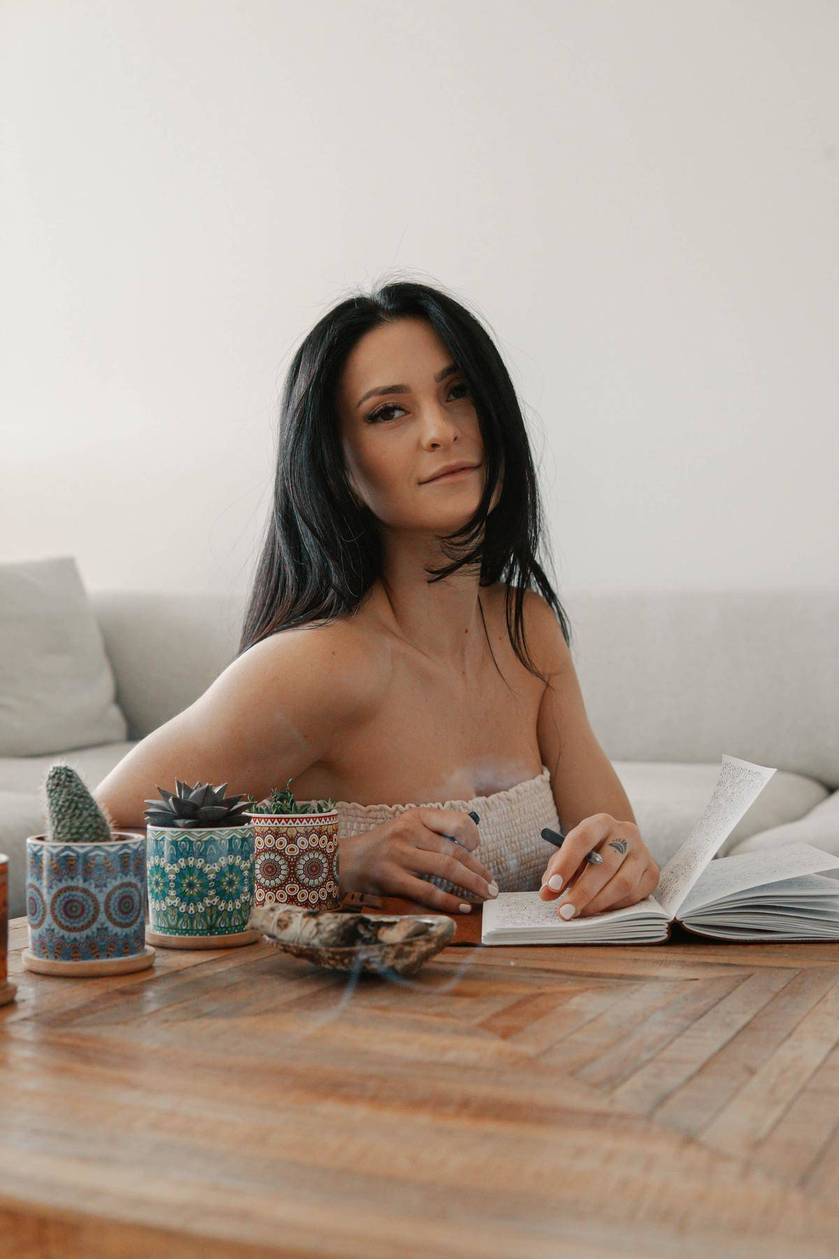 Woman seated on ground at coffee table writes in book