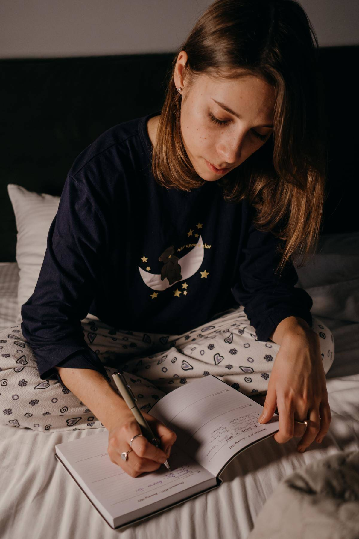 Woman writes in book seated in bed