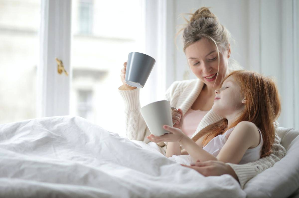 Mom and daughter in bed with mugs