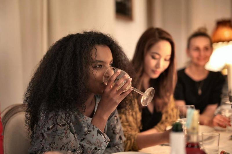 Woman sips wine at friend's dinner party