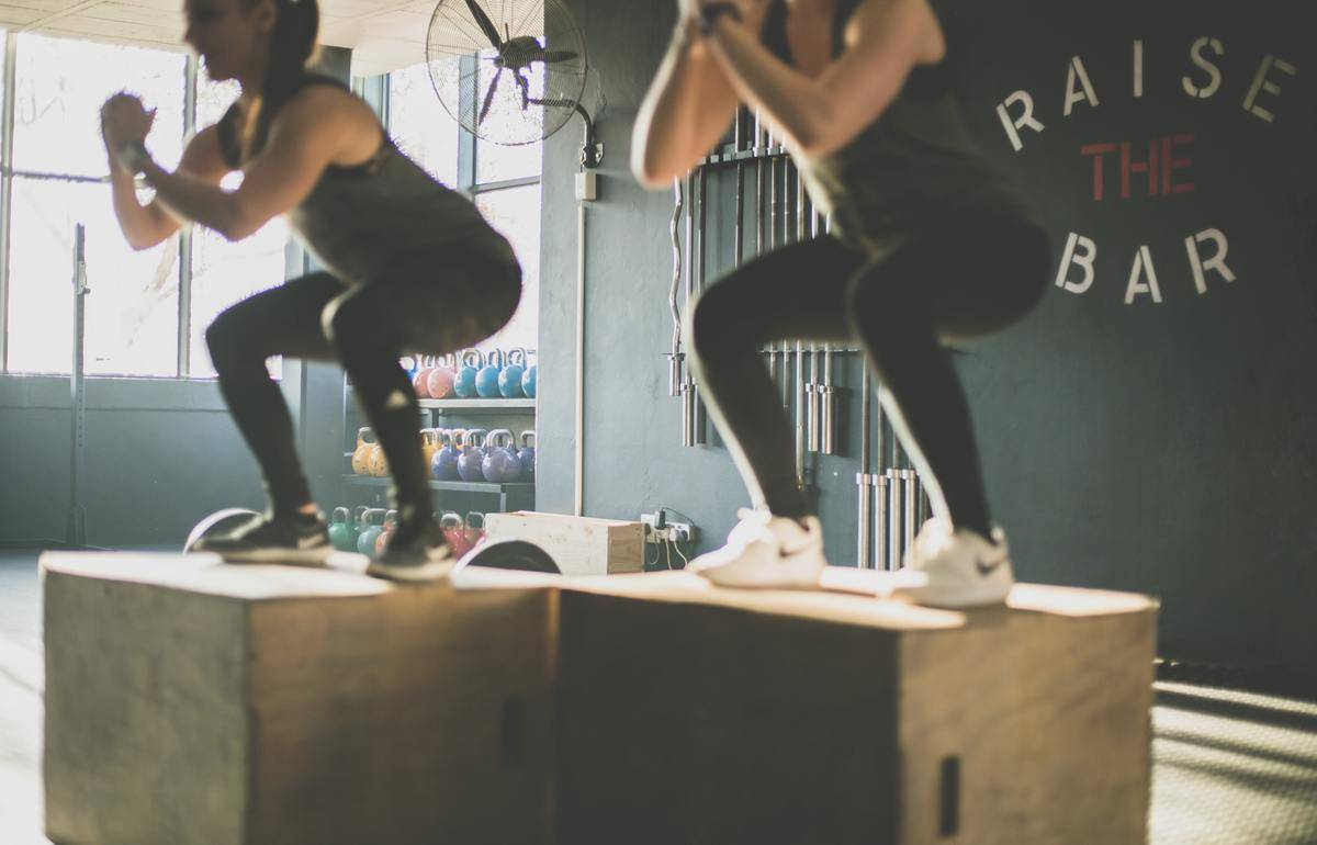Women do squats on large boxes