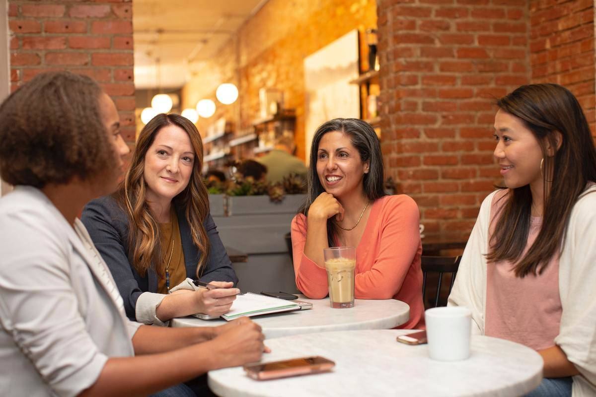 Women around table talking to each other