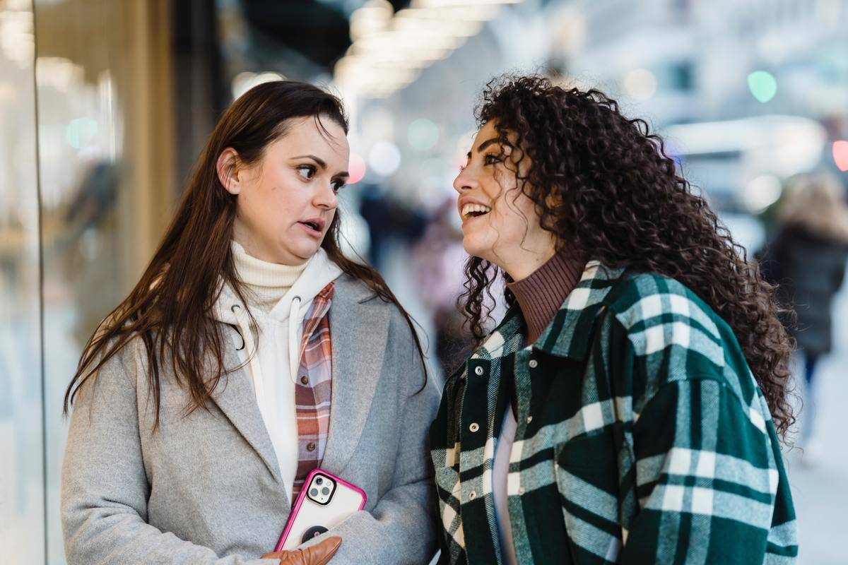One woman laughs, one woman looks more annoyed walking down street