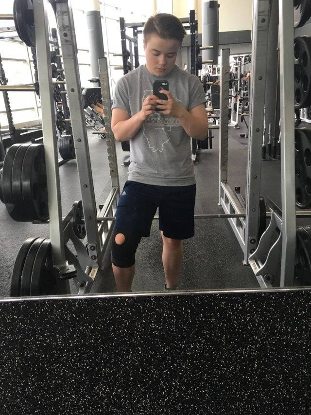 Man taking picture in the mirror in a gym