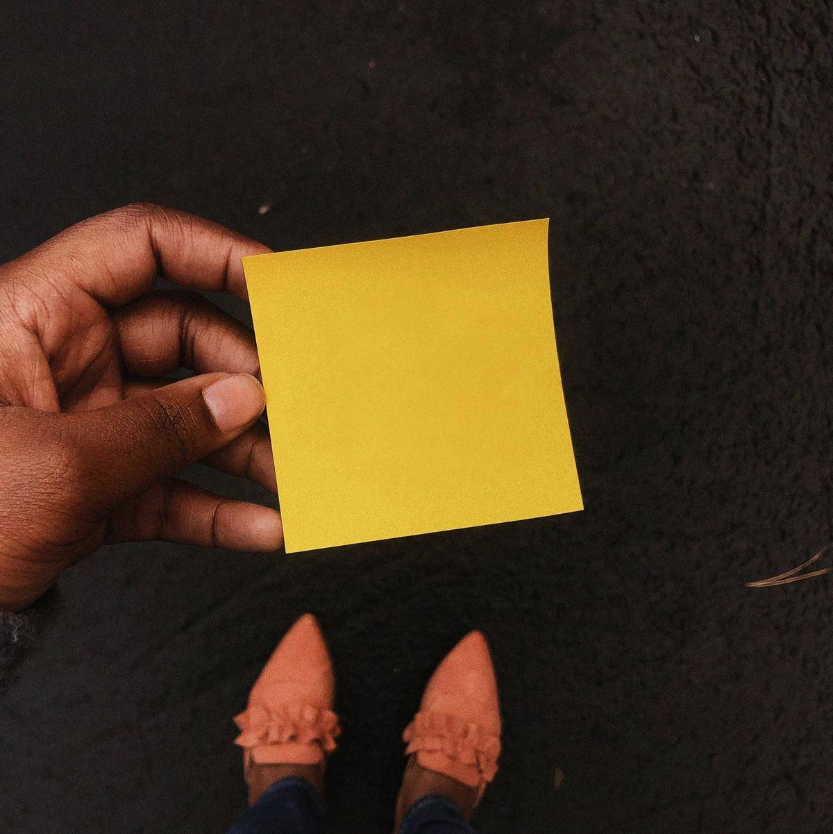 Close-up of a yellow sticky note a woman is holding in her hands.