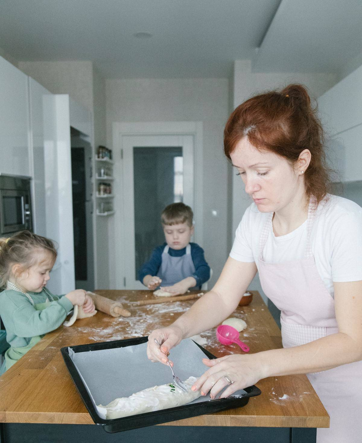 Young family in kitchen, mom baking, two kids helping