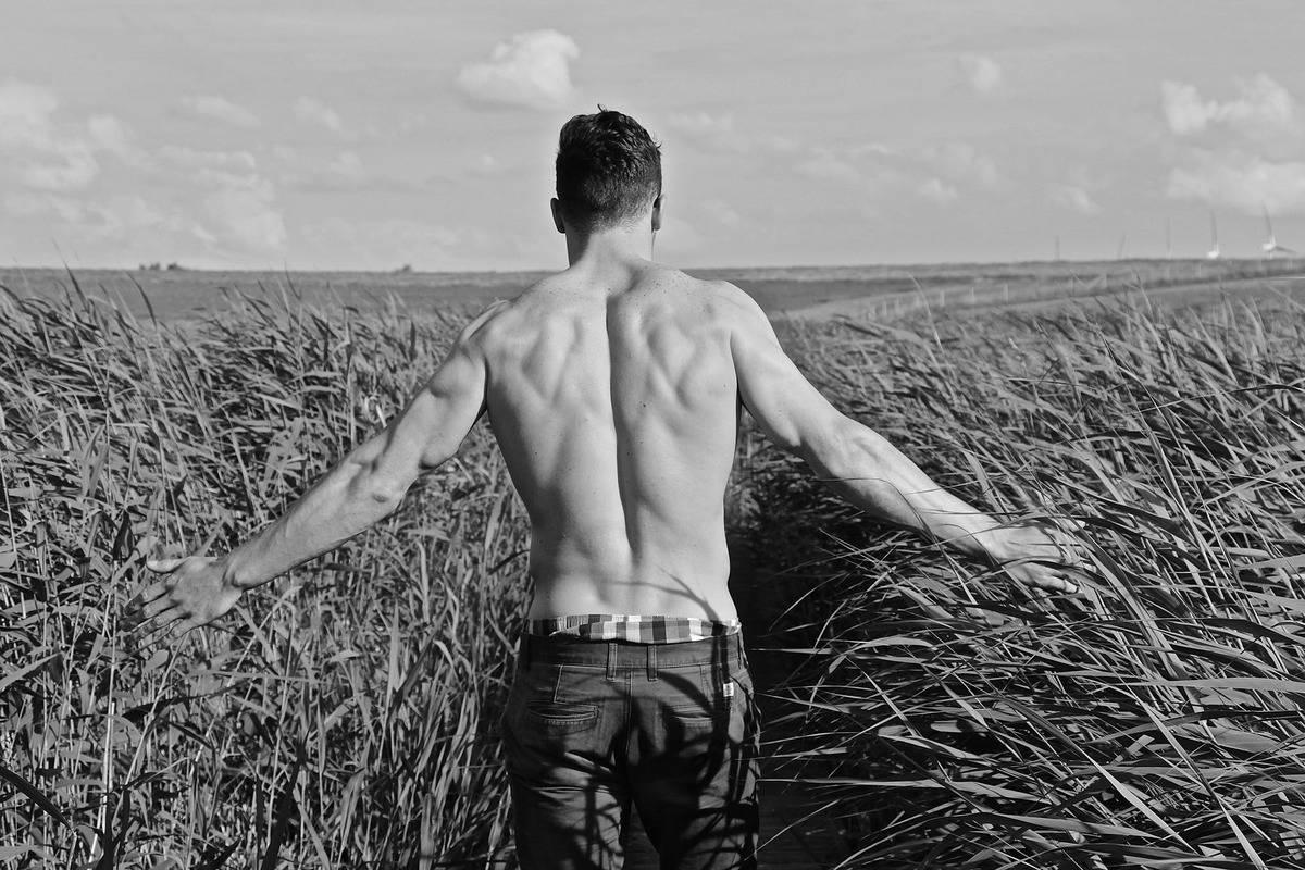 shirtless man walking through field