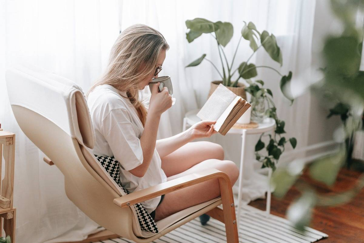 woman reading in chair while drinking coffee