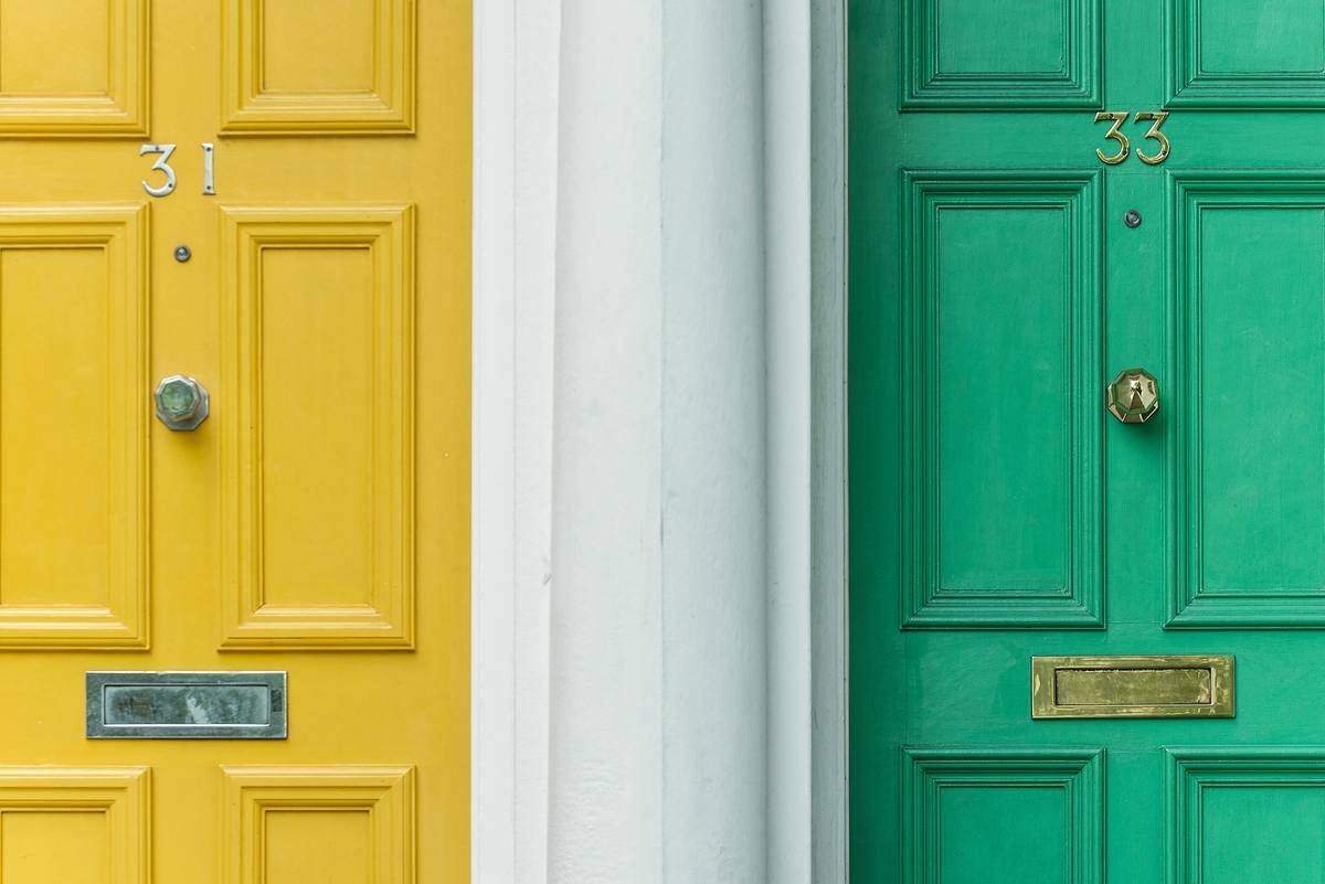 Two unit doors beside each other, one is yellow and one is green