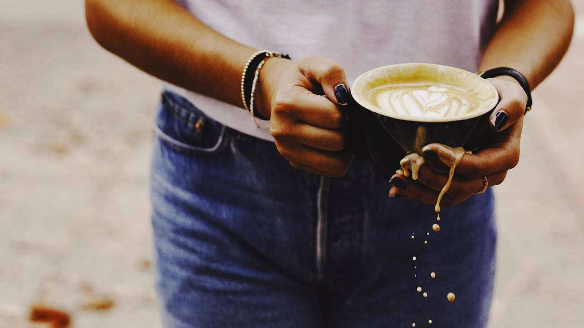 Hand holding coffee spilling out of mug