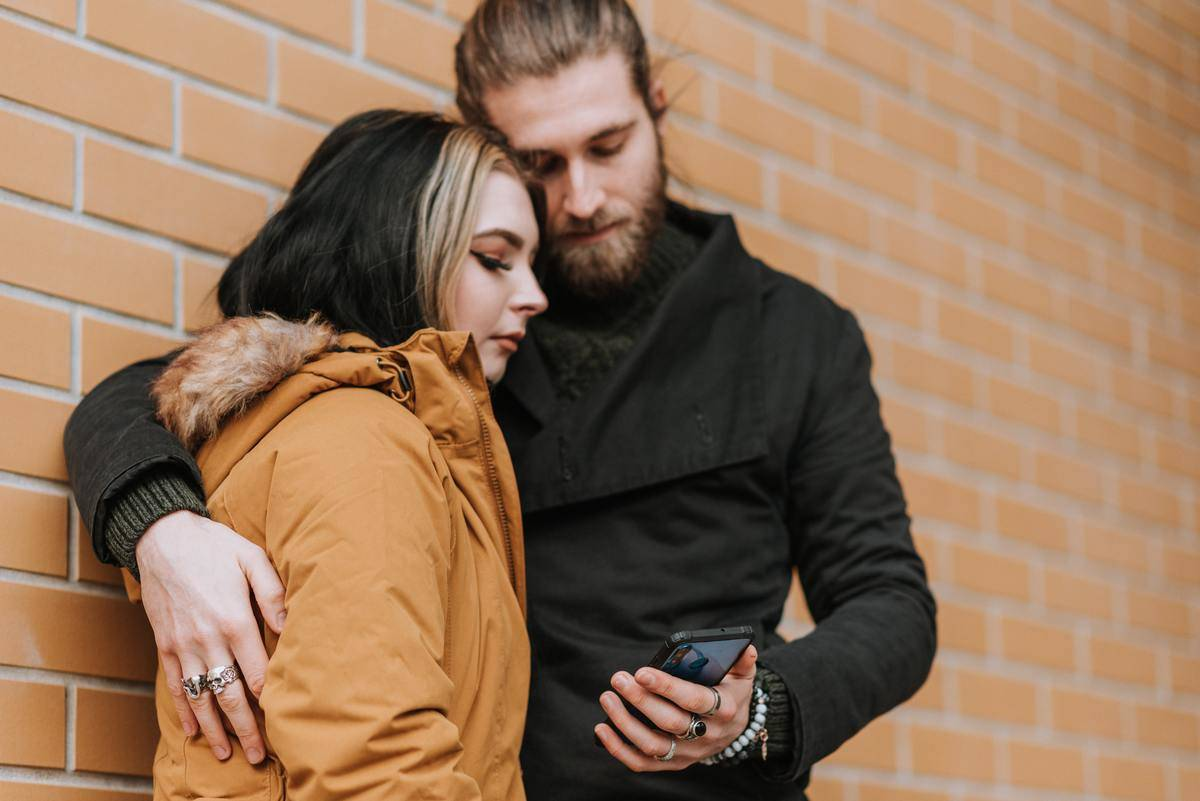 Woman leaned against man, both look at a cell phone
