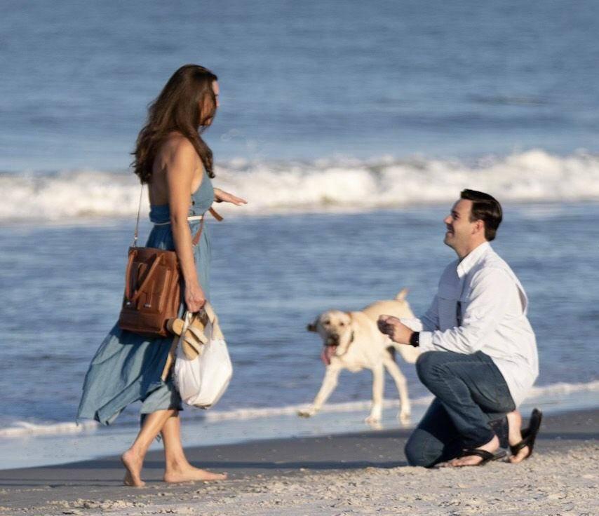 Dog photobombing engagement at the beach