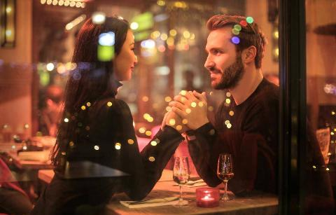 Couple sits at a table holding hands while on a date together.