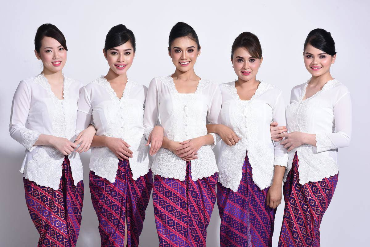 Flight attendants wearing white shirts, purple/red skirts, and wearing their hair in a tight bun.