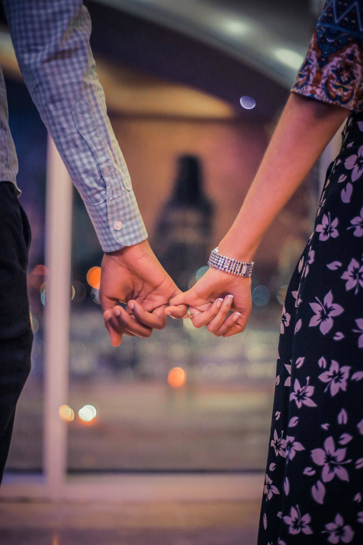 man and woman holding hands by their pinkies