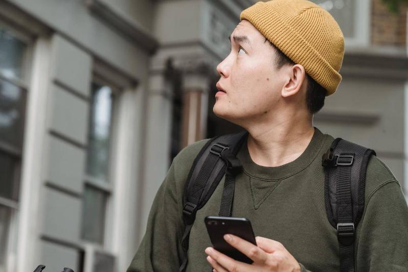 Man holding phone looks up at balcony