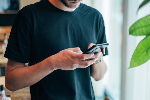Man looks down at phone sending text