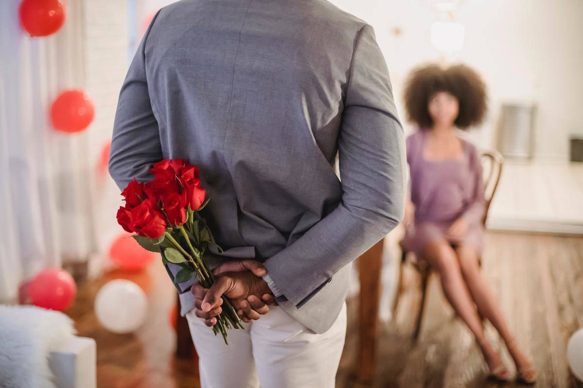 Man holds bouquet of red roses behind his back before giving them to his girlfriend.