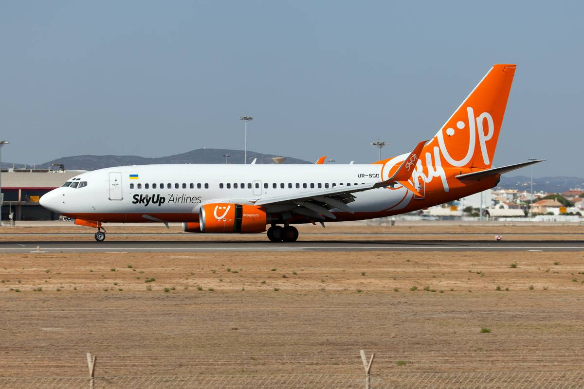 A SkyUp Airlines Boeing 737 touches down at an airport in Portugal.