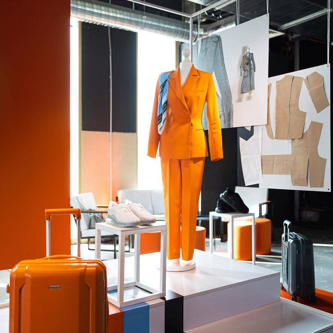 The new uniform of SkyUp Airlines flight attendants, including an orange blazer and trousers and white sneakers.