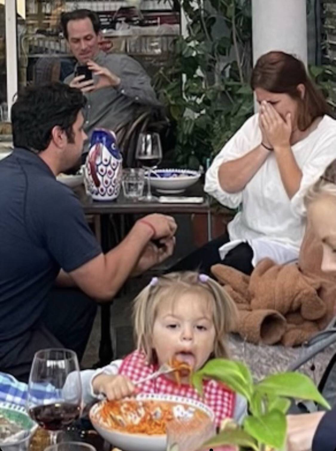 Engagement proposal at restaurant with toddler eating spaghetti in foreground