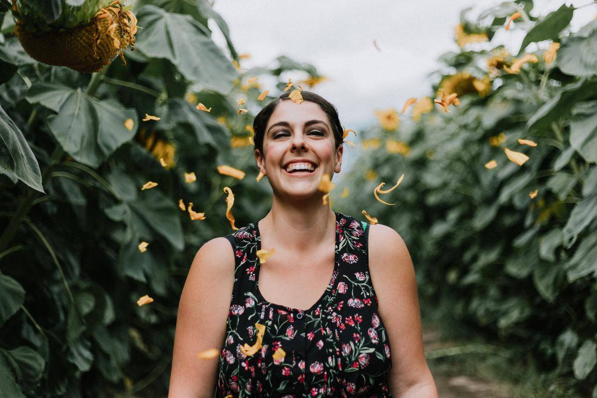 Woman looks at camera and smiles and is surrounding by a sunflower field.