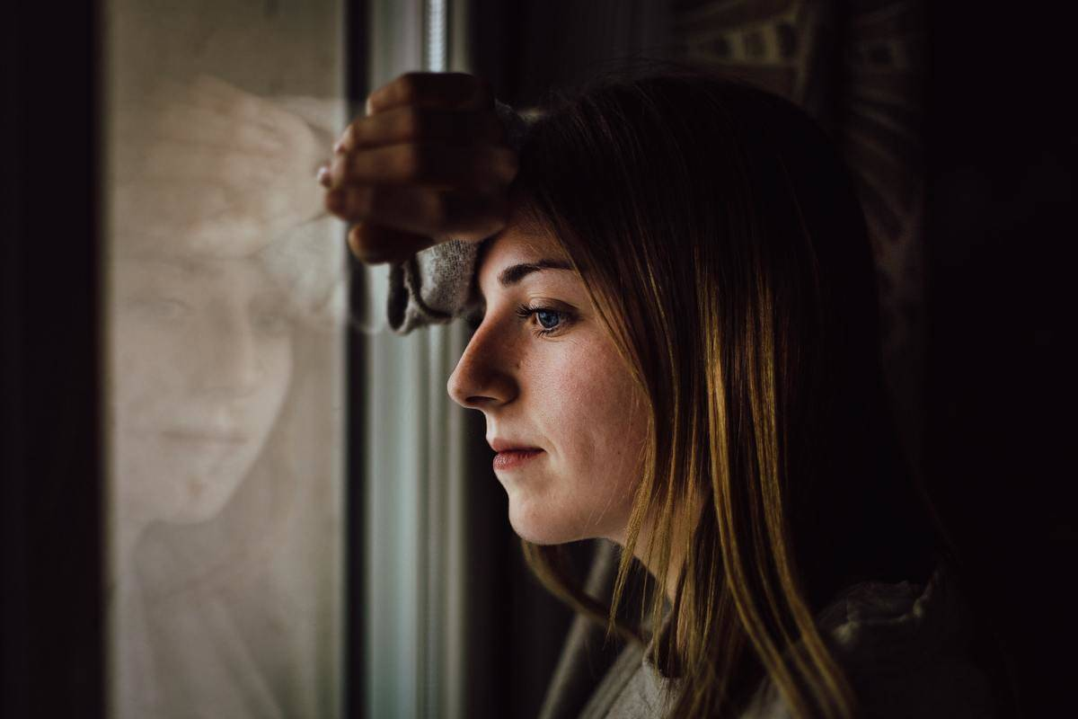 A woman looks out the window with a serious look on her face