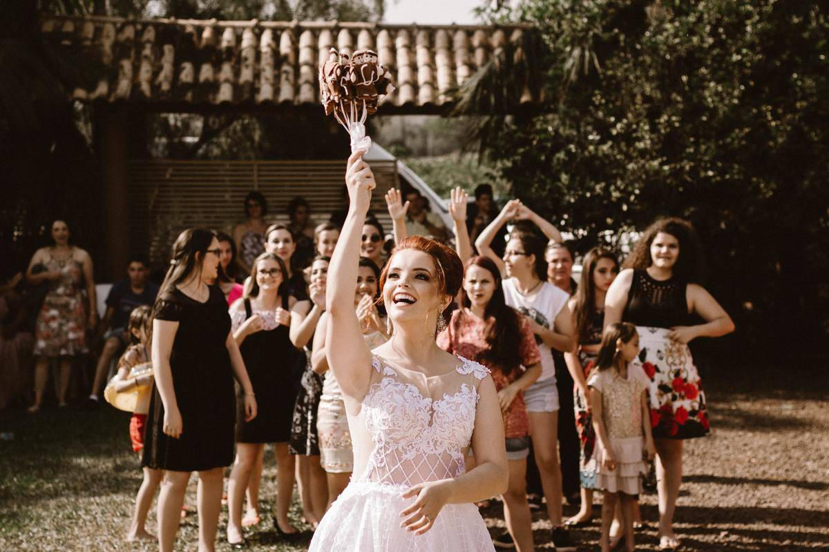 Woman throwing bouquet at wedding