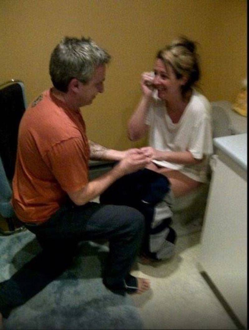 Woman sitting on toilet, man proposing to her