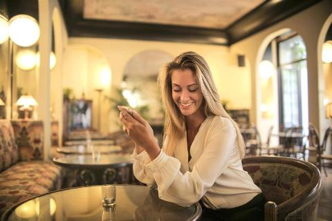 Woman smiles alone at phone in lobby