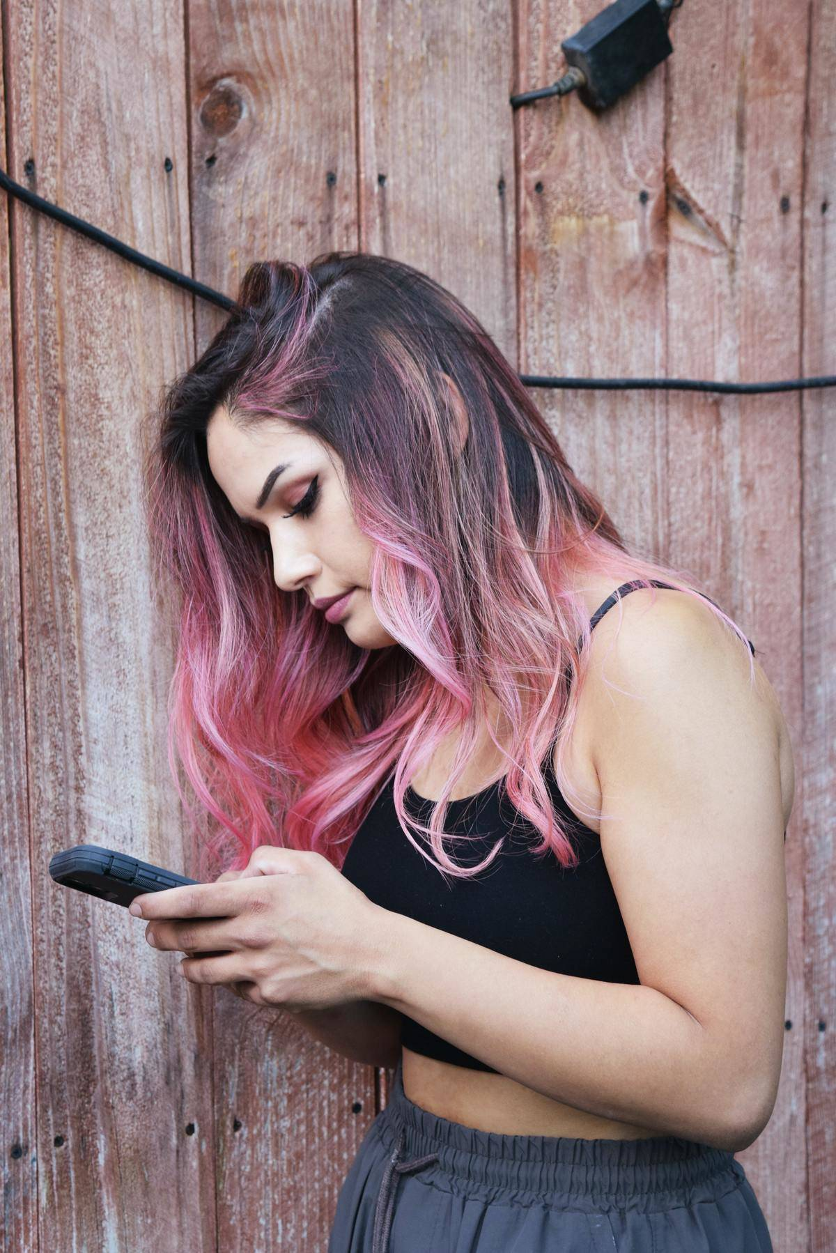 Woman with pink hair looks down at phone