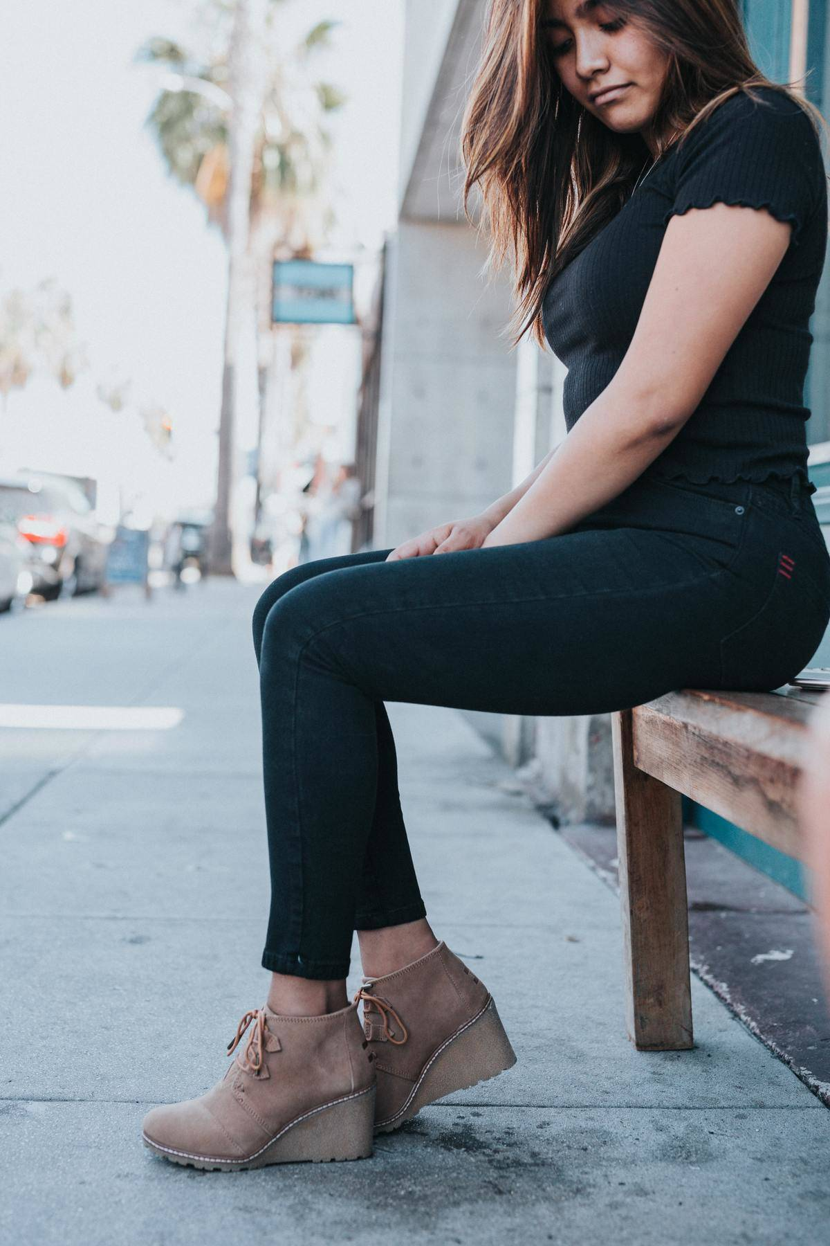 Woman dressed in a black t-shirt and jeans sits on a bench and looks down at her beige wedge shoes.