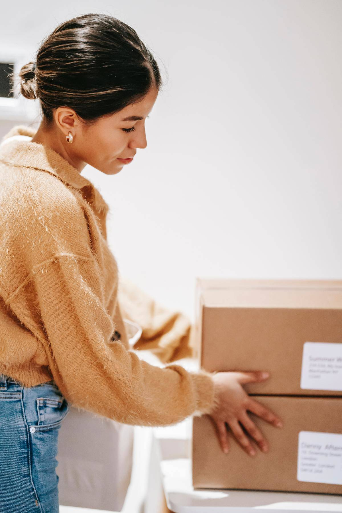 Woman looks at boxes smiling softly